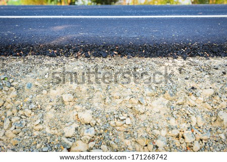 New asphalt road - Rock and soil material on the new paved road - stock photo