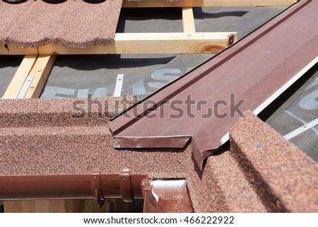 New asphalt shingle roof with brown rain gutter, wooden beams and vapour control layer