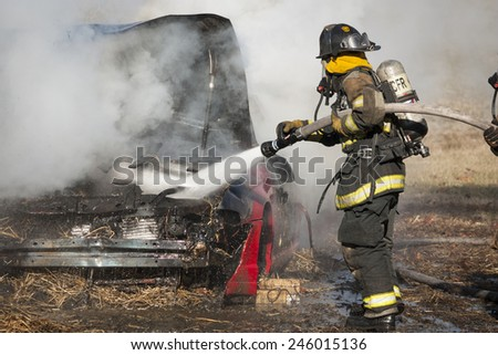 New Baltimore, Virginia, USA-January 17, 2015: Firemen training on a burning car at the New Baltimore Fire Station in New Baltimore, Virginia.