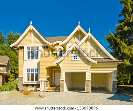 New big custom made luxury house under construction with double doors empty garage. Vancouver, Canada. - stock photo