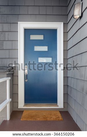New blue, white framed entry door with stainless steel door handle and small windows. New front door in grey home. - stock photo