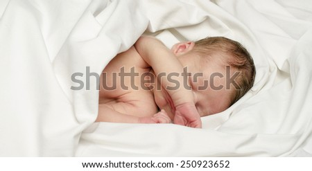 New born baby boy sleeping. Little baby taking a nap with the hand over his face. - stock photo