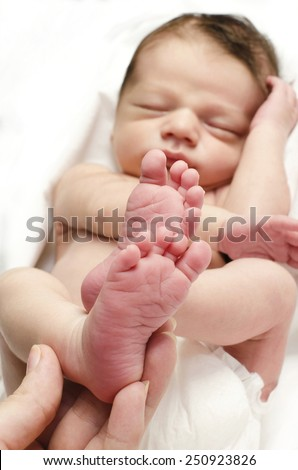 New born baby feet. Hand of the mother holding the sleeping baby boy little foot up. - stock photo
