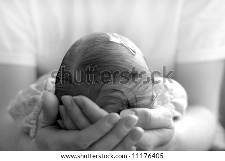 New born baby girl with a bow held by her mother - stock photo