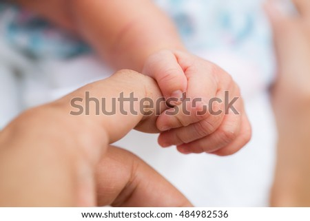 New born baby hold her father finger. Close up