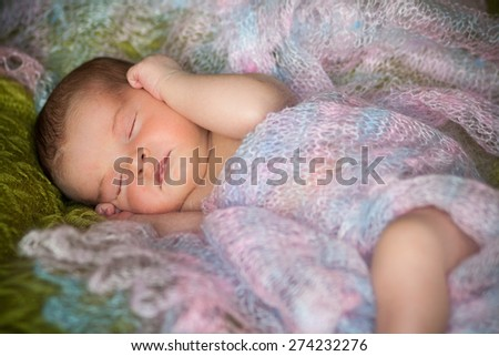 new born baby is lying in shawl, sleeping baby, eyes are closed, on blanket - stock photo