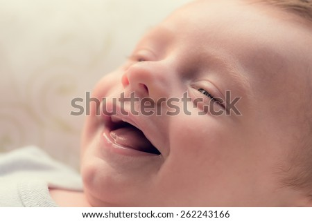 New Born baby laughing in natural light - stock photo