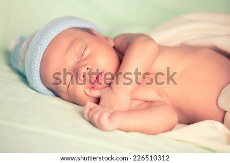 New born baby peacefully sleeping, Cross process tone - stock photo