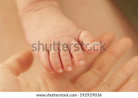 new born baby's foot and mother's hand