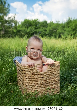 New born baby sit in basket on green grass - stock photo