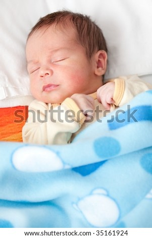 New born baby sleeping in bed - stock photo