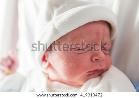 New born boy baby sleeping in the cod just after being born - stock photo