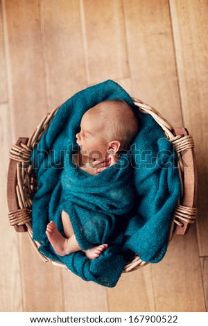 new born child in basket with blanket - stock photo