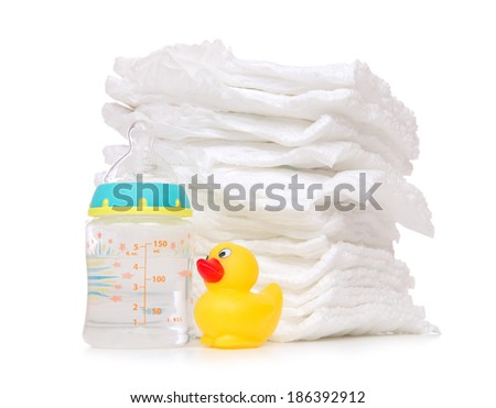 New born child stack of diapers, nipple soother, baby feeding milk bottle with water and yellow duck on a white background - stock photo