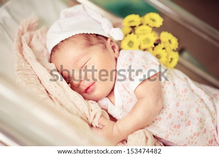 new born infant asleep in the blanket in delivery room  - stock photo