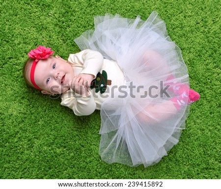 New born Infant child baby girl lying happy smiling on green grass blanket background - stock photo