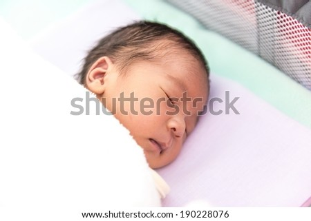 New born male Thai baby in various sleeping action, taken without flash - stock photo