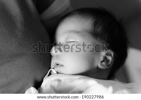 New born male Thai baby in various sleeping action, taken without flash in black and white - stock photo