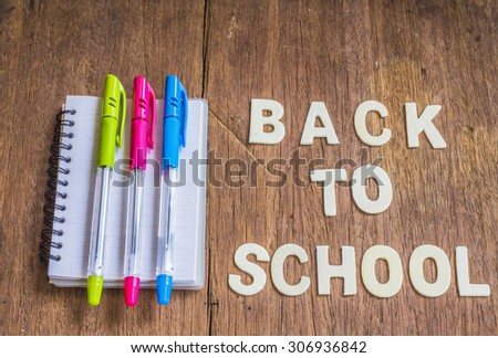 "New brand pens on the note book with the word "" back to school "" design by white letterpress on wooden  background - stock photo"