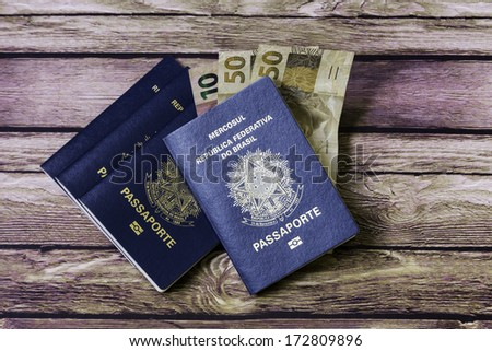 New Brazilian Passport and some brazilian money on the wooden table - stock photo