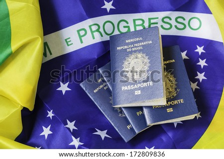 New Brazilian Passport and the flag of Brazil as the background - stock photo