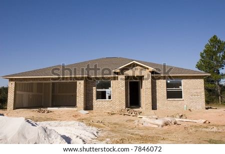 New brick house under construction with sand pile in front