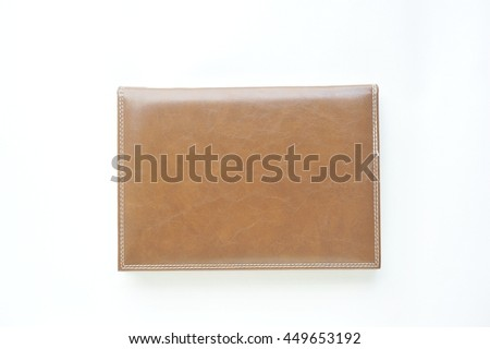 New brown leather notebook on white paper background.
