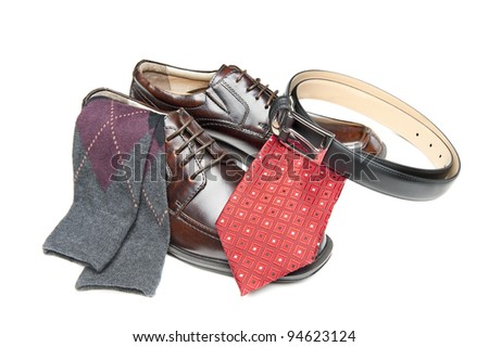 New brown leather shoes with red necktie and Argyle socks on white