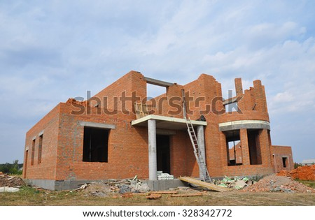 New  Building  Brick House Construction with Doorway Columns and Windows frame Exterior. Building Site Outside. - stock photo