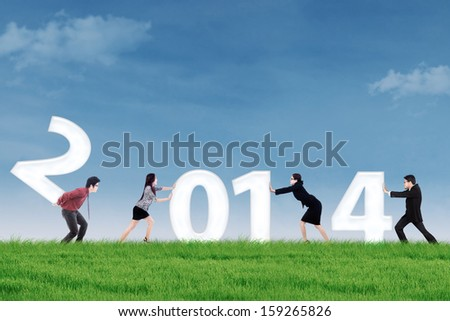 New business arrangement concept with bussiness people arrange a new year of 2014 - stock photo
