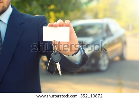 New car and business theme: a man in a black suit holds the keys of a new car and business card on a background of green tree