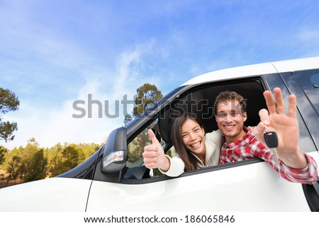 New car - happy couple showing car keys driving having fun on road trip drive in rental car. Happy lifestyle with beautiful young interracial couple outdoors on travel. Man driver and woman passenger. - stock photo