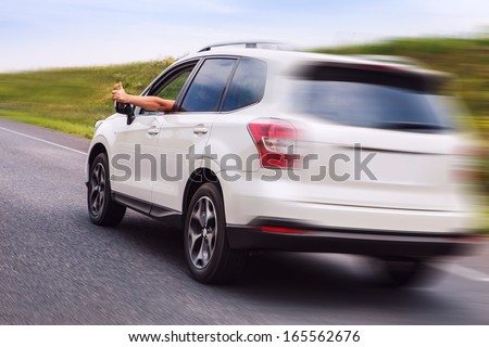 New car Happy owner rides the highway and shows thumb up - stock photo