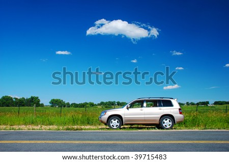 New car parked by the side of a lonely road in rural country - stock photo