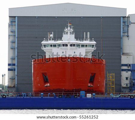 new Cargo ship in front of a shipyard hall - stock photo