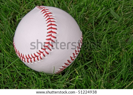 new,clean baseball in a grass background