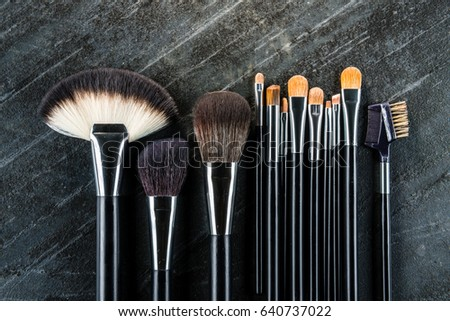 new clean professional cosmetic brush set put on black stone texture floor background for artist using makeup model with high angle view photo.