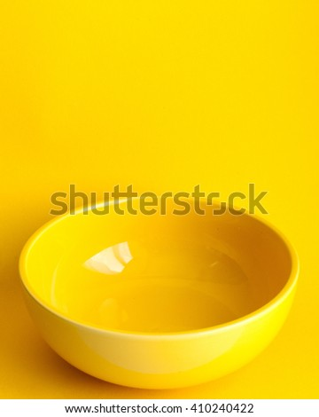 New clean yellow bowl on yellow background. Frontal view - stock photo