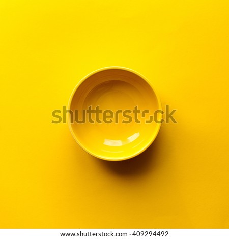 New clean yellow bowl on yellow background. Top view - stock photo