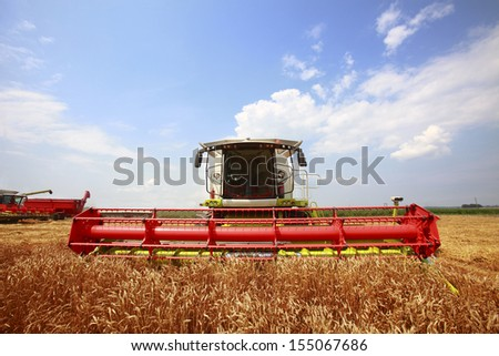 New combine harvester working in a wheat field - stock photo