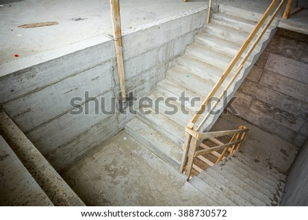 New concrete staircase with temporary wooden handrail, under construction. - stock photo