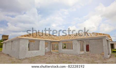 New Construction. Cement Block house with wooden roof truss. Blue sky and clouds in background. - stock photo
