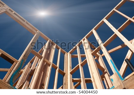 New Construction Framing Abstract with Sunburst Over Clear Blue Sky. - stock photo