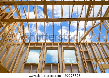 New construction home framing against sky - stock photo