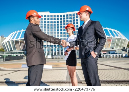 New construction transactions. Three confident business architect in protective helmet standing on the court and shake hands with each other - stock photo