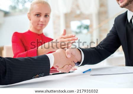 New contract. Three successful and confident businesspeople shake hands. Businesspeople in formal dress sitting in an office at a desk and smiling at the camera