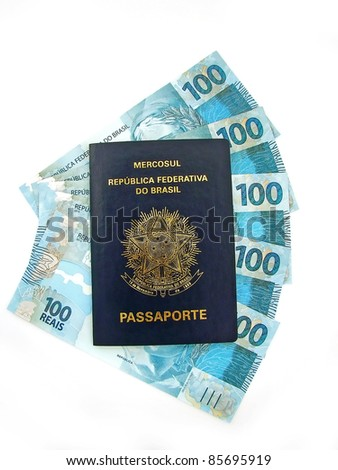 New currency from Brazil inside passport - stock photo