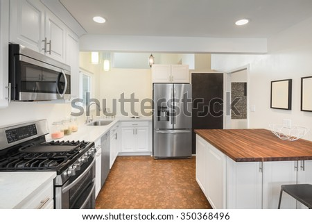 New decorated white Kitchen in luxury home with white marble counter top, kitchen island, stainless steel appliances and amazing new Cork Floor. - stock photo