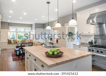 New decorated white large Kitchen in luxury home with timbered wooden counter top, kitchen island, modern stainless steel integral gas oven and extractor fan. - stock photo