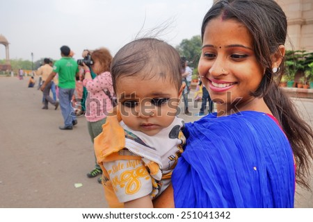 New Delhi 15 April 2014 : Mother and daughter on the street near India Gate. The picture show heavy henna eye stain on the little girl.